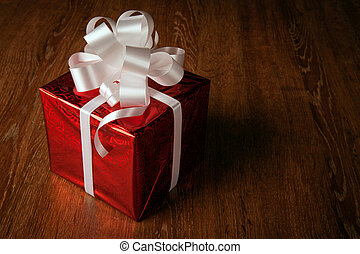 One red festive gift box with a white bow on a wooden table