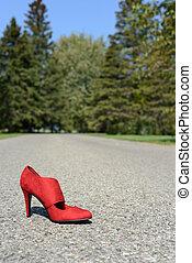 red high heel shoe on road