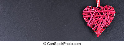 One red love heart isolated on black