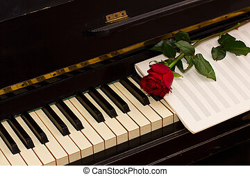 one red rose with notes paper on vintage piano
