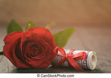 one red roses and bunch of dollars