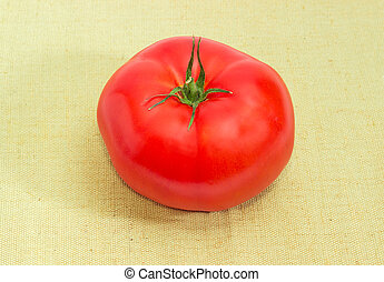 One red tomato closeup on a cloth
