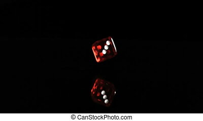 One red translucent dice in a super slow motion turning