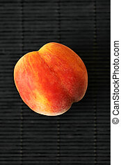 One ripe peach in on a black background. Summer fruit