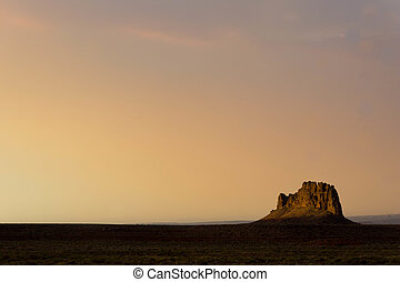 one rock mesa under a sunset sky in the desert