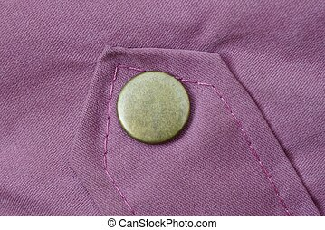 green iron button rivet on the red fabric sleeve on the clothes