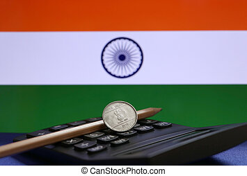 One Rupee coin of India on the calculator and pencil with Indian flag background.