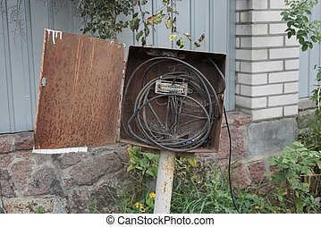 one rusty open iron box with electrical black wires