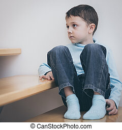 one sad little boy sitting on the stairs in house at the day time