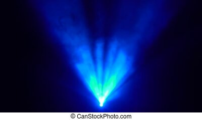 One searchlight in the center of the scene shines blue in...