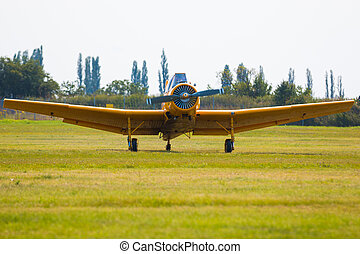 One seat single engine yellow civil utility aircraft in airport on grass