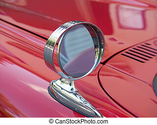one side mirror on a red car one beutiful thunderbird