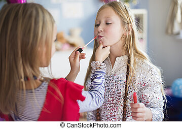 One sister helping another with doing make up