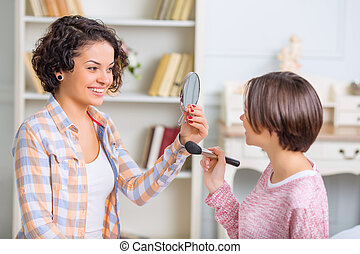 One sister helping another with make up.