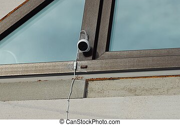 one small surveillance camera hanging on a brown window frame
