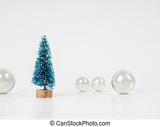 one small toy Christmas tree on the background of transparent balls, minimalistic card for the new year and Christmas