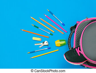 One sneaker sticks out of a school backpack and school supplies on a blue table. Flat lay.