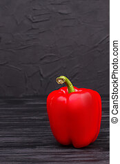 One sweet red bell pepper on black wooden table.