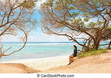 One teen girl sitting alone on beach under trees