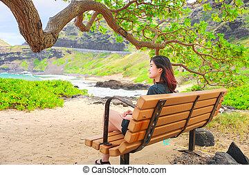 One teen girl sitting on bench at Makapu'u beach park