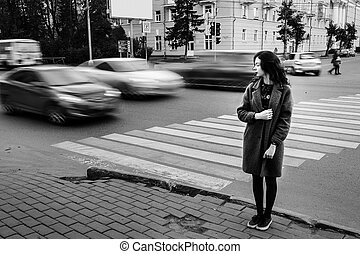 One teenage girl blue coat standing at the traffic light on...