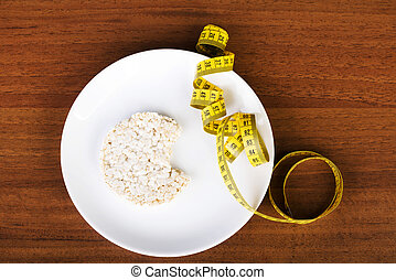 One waffle rice on a plate and measuring tape.
