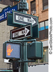 One way street sign pole in New York with red traffic light