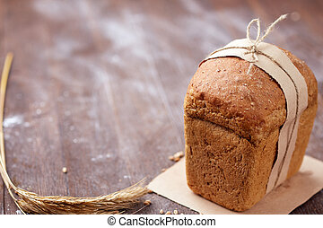 One white bread with flour on a wooden background. Advertising bread. Leaning flour.