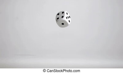 One white dice in a super slow motion rebounding