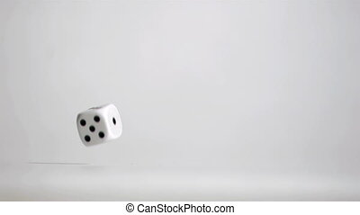 One white dice in super slow motion rebounding and turning on the grey floor