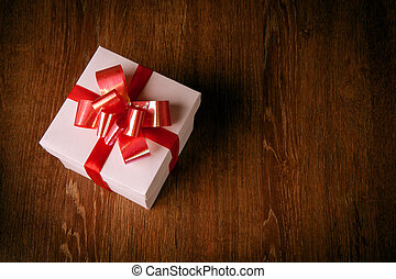 One white festive gift box with a red bow on a wooden table