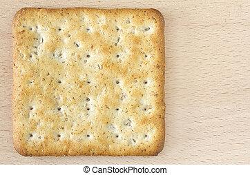 One wholegrain cracker on wooden board