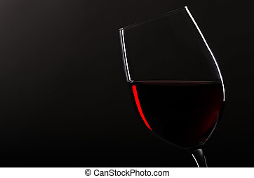 wineglass with redwine before black background - one...