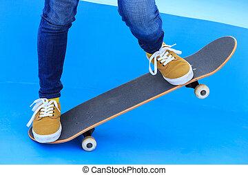 one woman skateboarder legs riding skateboard on skatepark