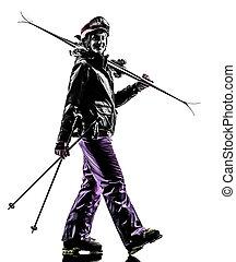 one woman skier walking silhouette - one caucasian woman...