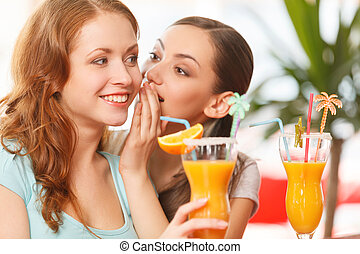 one woman whispering something to friend. two girls sitting in cafe and drinking juice