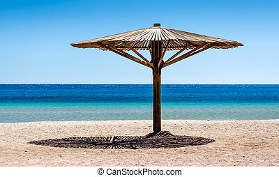 one wooden beach umbrella on the sand on the beach against the blue water of the Red Sea in Egypt Dahab South Sinai
