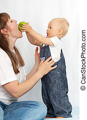 One year old baby feeds her mother an apple.