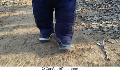 One year old baby walks. Walk a small child. Feet go on the...