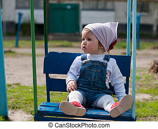 one year-old girl on a swing