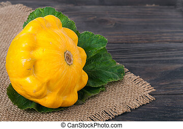 one yellow squash on a wooden background with napkin of burlap