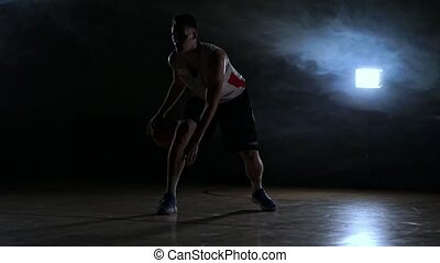 one young adult man, basketball player dribble ball, dark...
