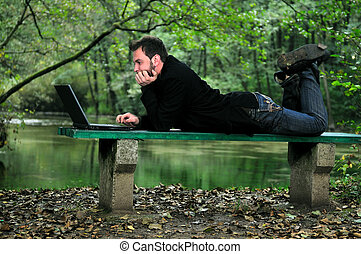 young businessman working on laptop outdoor
