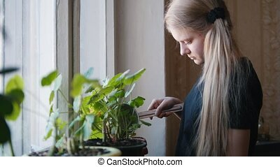 One young girl watering flowers at home