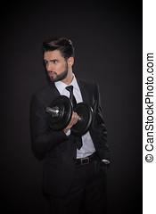 one young man dumbbell, black background, suit elegant
