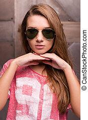 ongedwongen, beauty., mooi, jonge vrouw , in, zonnebrillen, holdingshanden, op, kin, en, kijken naar van fototoestel, terwijl, staand, tegen, metaal, achtergrond