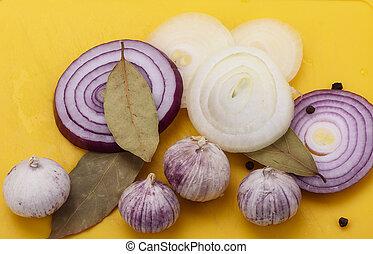 Onion, garlic, bay leaf with pepper on a yellow cutting board