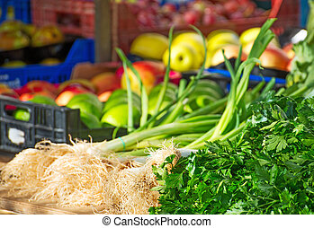 Onion, parsley and fruits on the market.
