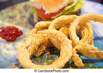Onion Rings with Hamburger in Background