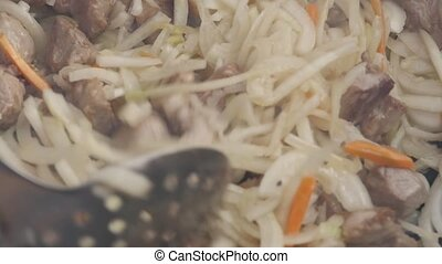 onions and garlic are fried in a pan with meat. Cooking stir-fried meat with vegetables. slow motion